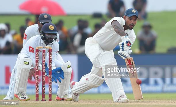 Indian batsman Shikhar Dhawan plays a shot as Sri Lankan wicketkeeper Niroshan Dickwella looks on during the first day of the first Test match...