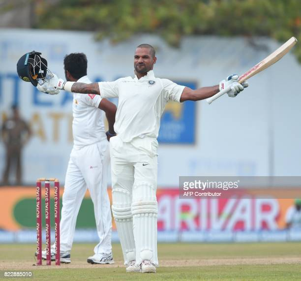 Indian batsman Shikhar Dhawan raises his bat to the crowd after scoring a century during the first day of the first Test match between Sri Lanka and...