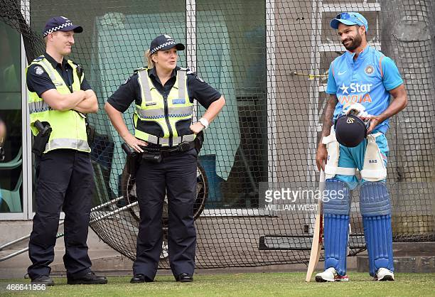 Indian batsman Shikhar Dhawan speaks to two police officers during a training session ahead of their 2015 Cricket World Cup quarterfinal match...