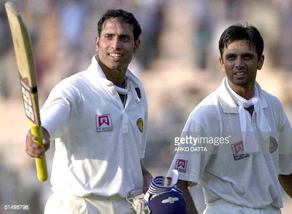 Indian batsman Venkat Sai Laxman points his bat towards the cheering crowd as teammate Rahul Dravid looks on as they walk back to the pavillion on...