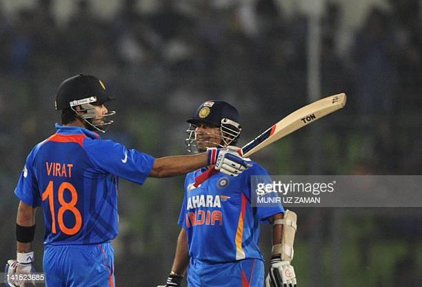 Indian batsman Virat Kholi gestures after scoring a half century as his teammate Sachin Tendulkar looks on during the one day international Asia Cup...