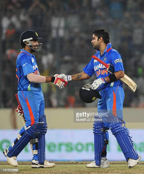 Indian batsman Virat Kholi shakes hand with his teammate Rohit Sharma after scoring a century during the one day international Asia Cup cricket match...