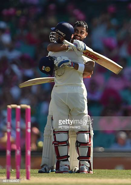 Indian batsman Virat Kohli celebrates his century with innings partner Wriddhiman Saha during day three of the fourth cricket Test between Australia...