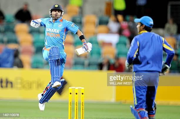Indian batsman Virat Kohli leaps in the air after scoring his century against Sri Lanka as Kumar Sangakkara looks on in their international one day...