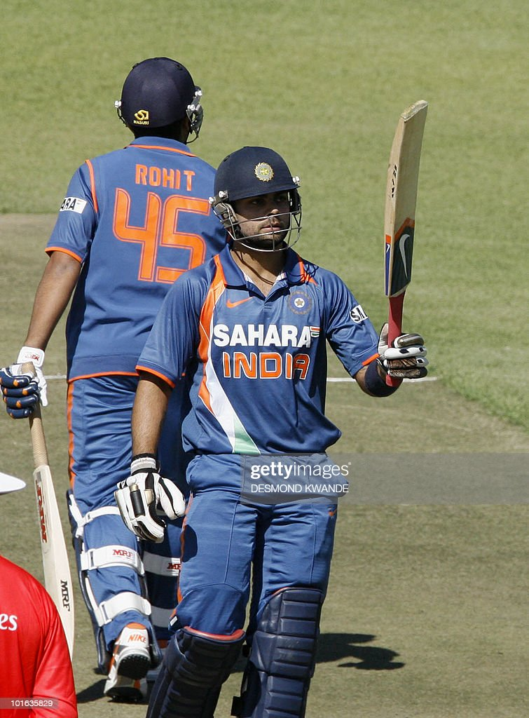 Indian batsman Virat Kohli (R) raises the cricket bat after his 50th at Harare Sports Club on June 5, 2010 in the fifth match of the Micromax Cup Triangular One-Day series hosted by Zimbabwe. AFP PHOTO / Desmond Kwande