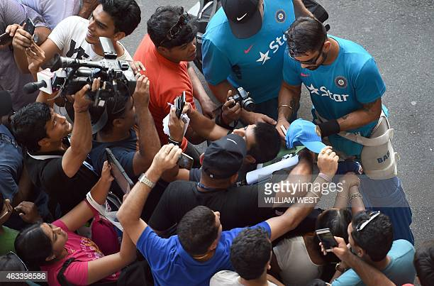 Indian batsman Virat Kohli signs autographs for the fans after their final training session for the 2015 Cricket World Cup in Adelaide on February 14...