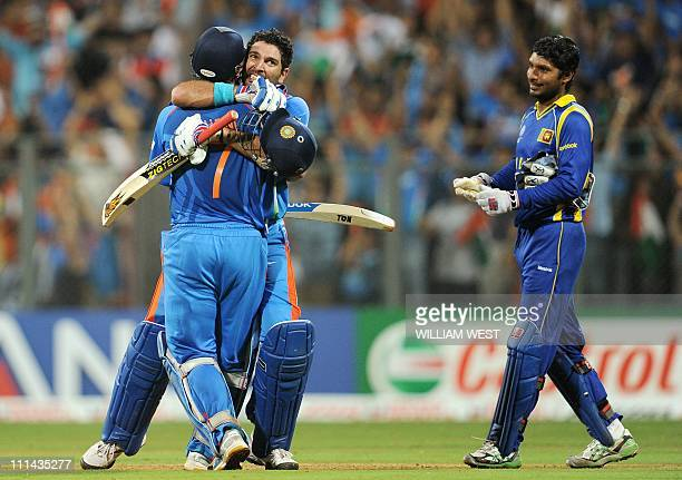 Indian batsmen Yuvraj Singh embraces Mahendra Singh Dhoni as Sri Lankan captain Kumar Sangakkara looks on after India defeated Sri Lanka in the ICC...