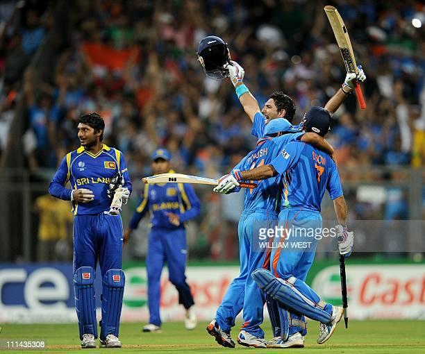Indian batsmen Yuvraj Singh raises his bat with Mahendra Singh Dhoni as Sri Lankan captain Kumar Sangakkara looks on after India defeated Sri Lanka...