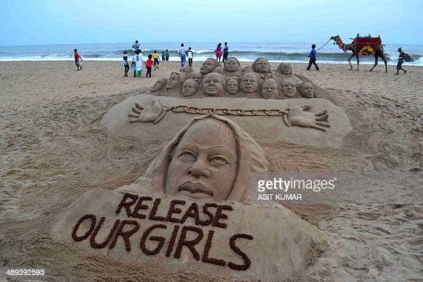 Indian beachgoers pass a sand sculpture calling for the release of kidnapped school girls in Nigeria which has been created by sand artist Sudarsan...