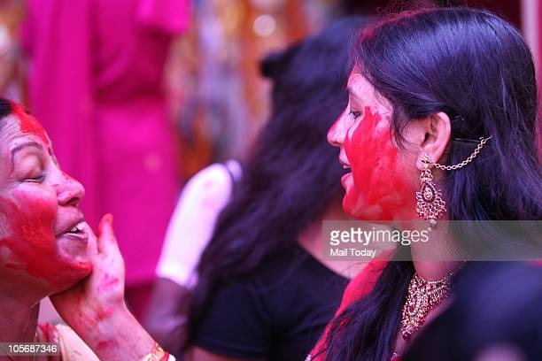Indian Bengali women apply Sindoor on each other's faces during a ritual called 'Sindoor Khela' on the occasion of the Dusshera or Vijaya Dashami...