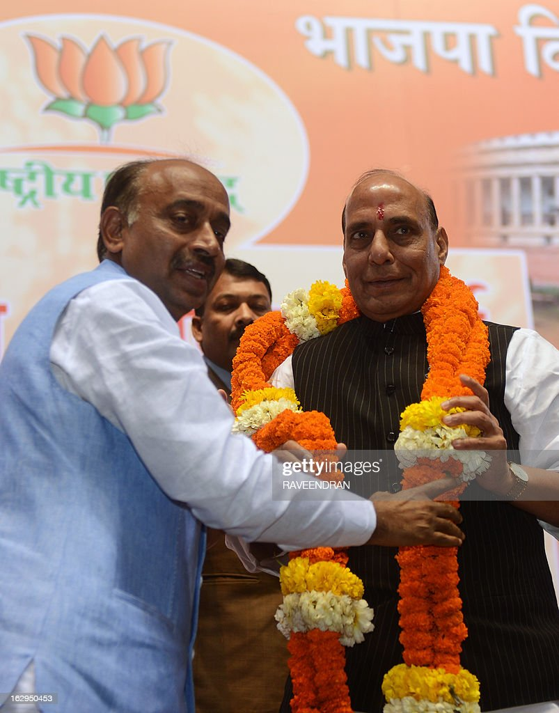 Indian Bharatiya Janata Party (BJP) Delhi President Vijaya Goyalo (L) garlands BJP President Rajnath Singh during a BJP National Council meeting in New Delhi on March 2, 2013. The two day BJP party meeting was held for the party to deliberate its road map in the run up to the next general elections in 2014, besides discussing the political and economic issues confronting the country. AFP PHOTO/ RAVEENDRAN