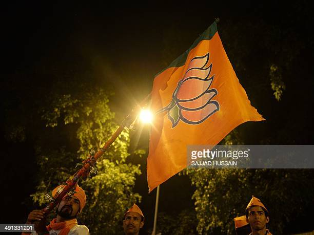 Indian Bharatiya Janata Party supporters hold up a flag with the lotus party symbol outside the party headquarters in New Delhi on May 16 2014...