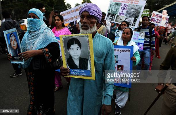 Indian Bhopal Gas disaster victim Barkat Ali holds a photograph of his daughter who was killed in the disaster during a commemoration rally in Bhopal...