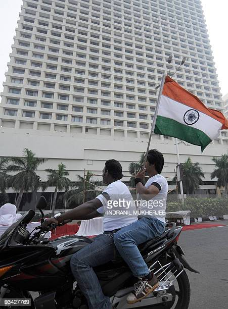 Indian bikers carrying the national flag ride past the Trident hotel one of the sites of last year's terror attacks in Mumbai on November 26 2009...