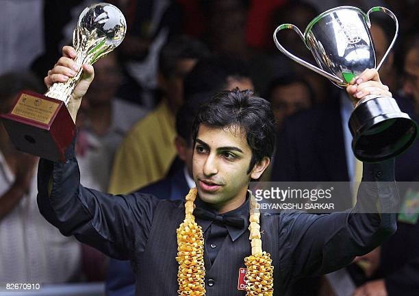 Indian billiards player Pankaj Advani lifts his trophies after winning his points final match against compatriot Geet Sethi during the International...