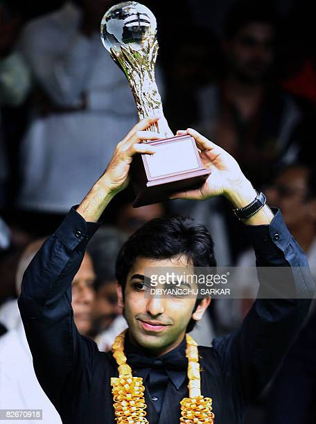 Indian billiards player Pankaj Advani lifts his trophy after winning his points final match against compatriot Geet Sethi during the International...