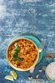 Indian Biryani rice dish with chicken meat, curry, cashew nuts and saffron. Top view, blank space, rustic background
