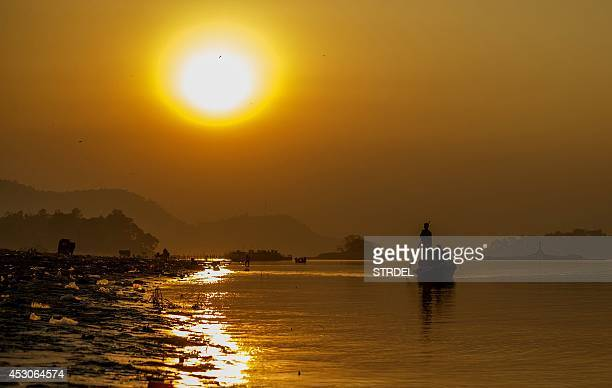 Indian boatmen paddle down the Brahmaputra River at sunset at Ujanbazar Ghat in Guwahati on August 2 2014 The Brahmaputra originates in Tibet where...