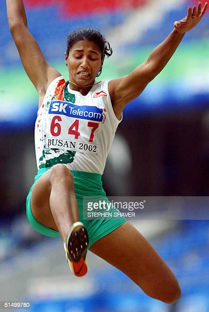Indian Bobby Anju George flies as she competes in the women's long jump during the 14th Asian Games in Busan 07 October 2002 George won with a jump...