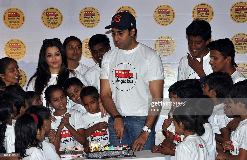 Indian Bollywood actor Abhishek Bachchan (C) poses with his wife Aishwarya Rai Bachchan (L) and a group of children on the occasion of Children's Day in Mumbai late November 14, 2012.