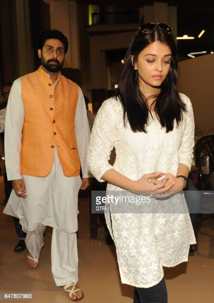 Indian Bollywood actor Abhishek Bachchan walks with his wife actress Aishwarya Rai Bachchan as they attend a prayer meeting for Veerappa Shetty the...