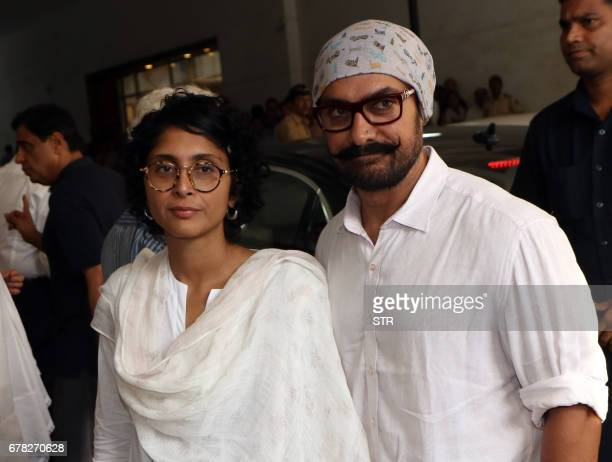 Indian Bollywood actor Amir Khan poses with his wife Kiran Rao Khan as they arrive to attend a prayer meeting for the late actor and politician Vinod...