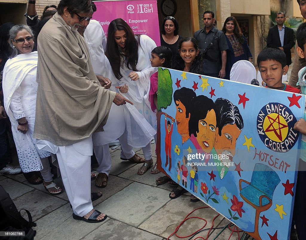Indian Bollywood actor Amitabh Bachchan (2L), accompanied by wife Jaya (L) and son Abhishek (3rd L, partly obscured) and his wife Aishwarya Rai Bachchan, is presented a piece of artwork from children during a press conference in Mumbai on February 9, 2013. The Bachchan family pledged to donate the proceeds of a book to the Plan India charity organisation, which supports the protection and rights of newborn girls in the country. Married women in India face huge pressure to produce male heirs, who are seen as breadwinners while girls are often viewed as a burden to the family as they require hefty dowries to be married off. AFP PHOTO/Indranil MUKHERJEE