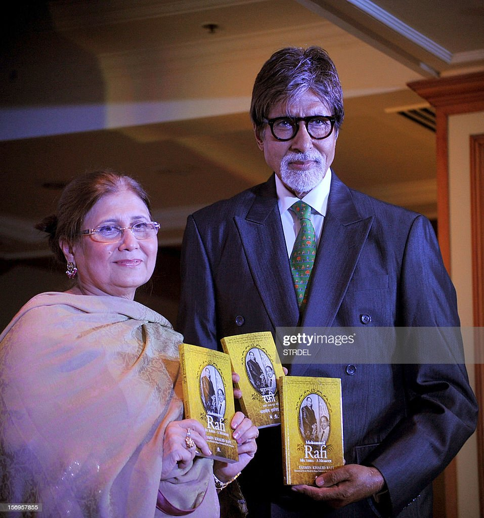 "Indian Bollywood actor Amitabh Bachchan (R) holds a copy of the book ""Mohammed Rafi My Abba- A Memoir"" by Yasmin K.Rafi (L) in Mumbai on November 25, 2012."