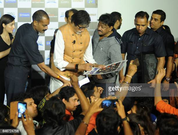 Indian Bollywood actor Amitabh Bachchan signs autographs watched by director Ram Gopal Varma during the launch of the forthcoming Hindi film Sarkar 3...