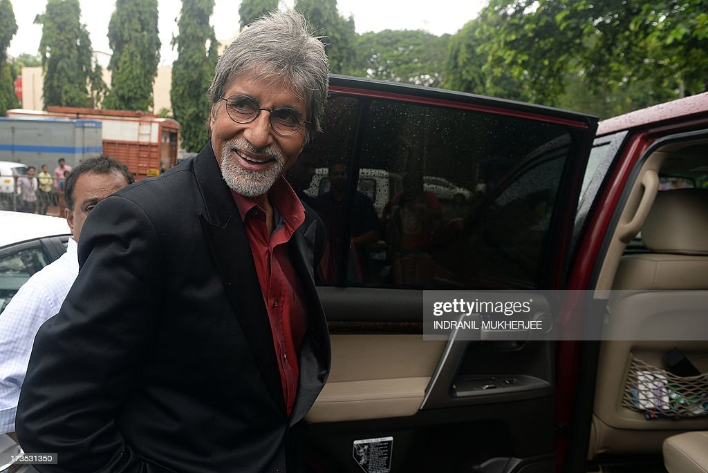 Indian Bollywood actor Amitabh Bachchan smiles as he enters his car while shooting a television commercial for a leading jewellery house in Mumbai on July 16, 2013. Bachchan, 71, is still one of the most sought after filmstars for endorsing brands from shampoo to shoe lace. Known universally as 'The Big B', Amitach Bachchan made his name as the 'angry young man' of Hindi cinema. He starred in more than 150 films including the 1970s hits 'Sholay' (Embers), 'Deewaar' (The Wall) and 'Don'.
