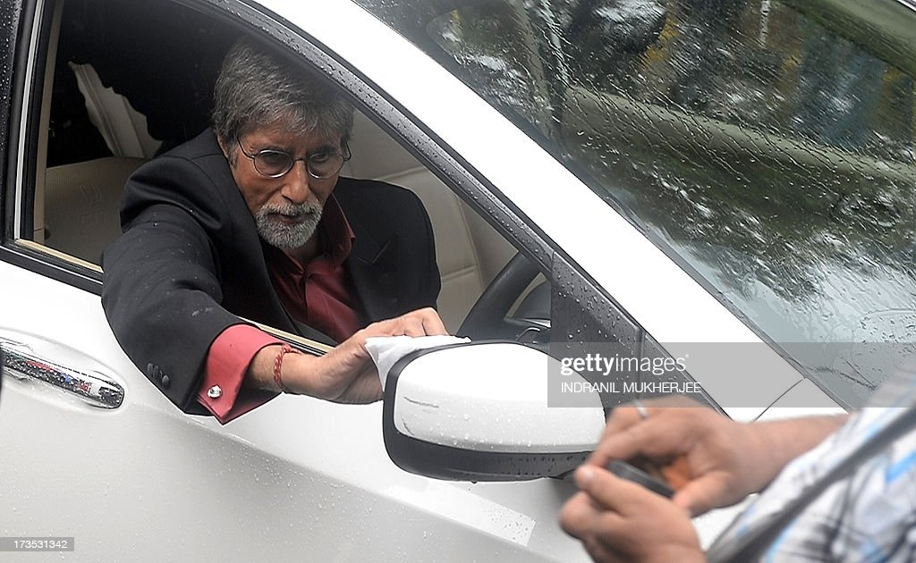 Indian Bollywood actor Amitabh Bachchan wipes rain-water off the mirror of a car as he shoots a television coomercial for a leading jewellery house in Mumbai on July 16, 2013. Bachchan, 71, is still one of the most sought after filmstars for endorsing brands from shampoo to shoe lace. Known universally as 'The Big B', Amitach Bachchan made his name as the 'angry young man' of Hindi cinema. He starred in more than 150 films including the 1970s hits 'Sholay' (Embers), 'Deewaar' (The Wall) and 'Don'.