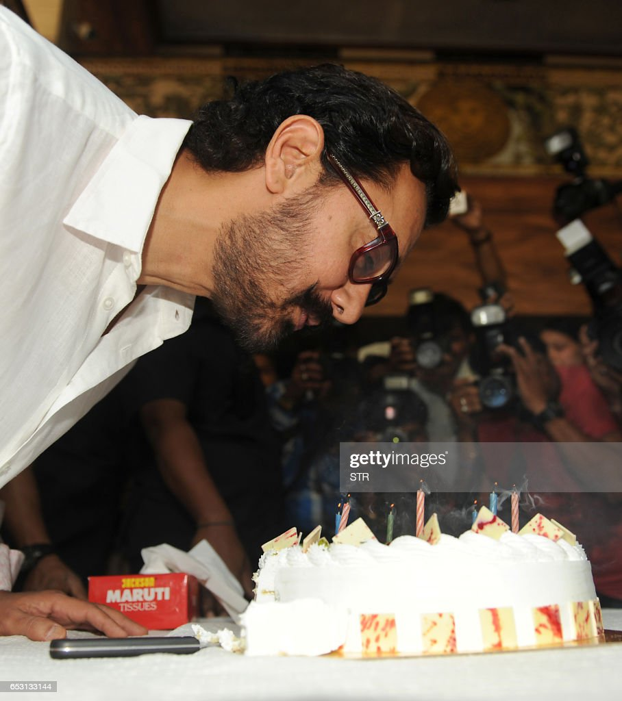 Indian Bollywood actor and producer Aamir Khan poses for the media during the cake cutting on his 52nd birthday, at his residence in Mumbai on March 14, 2017