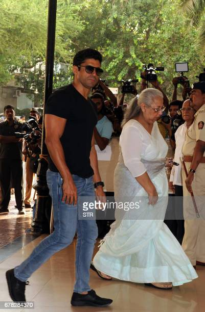 Indian Bollywood actor Farhan Akhtar walks with his mother Honey Irani as they arrive to attend a prayer meeting for the late actor and politician...