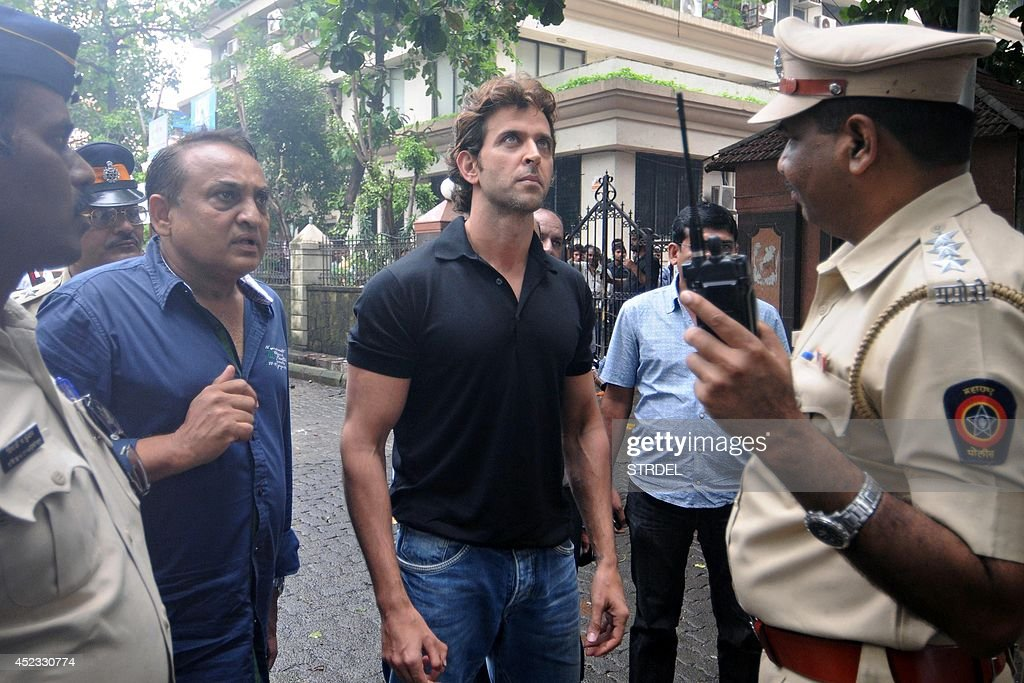 Indian Bollywood actor Hrithik Roshan (C) looks on at the damage to his office located in a 22-storey building that caught fire in Mumbai on July 18, 2014. Two helicopters from the Indian Navy and Coast Guard flew rescue missions to evacuate over a dozen firemen trapped in the burning 22-storey commercial building in a western Mumbai suburb, a report said. AFP PHOTO/STR