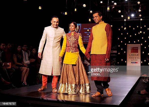 Indian Bollywood actor Rahul Bose and Indian author Chetan Bhagat pose with a model as they showcase creations by designer Vikram Phadnis during a...