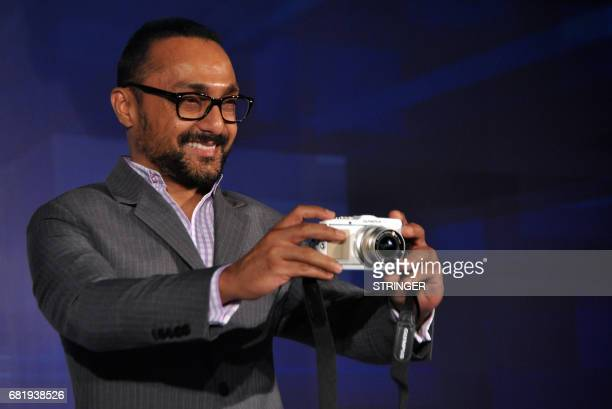 Indian Bollywood actor Rahul Bose holds an Olympus Trinity series camera during the product launch in Mumbai on June 30 2011 AFP PHOTO/STR / AFP...
