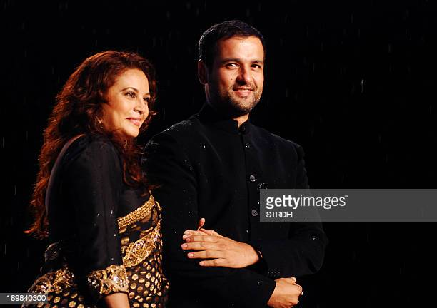 Indian Bollywood actor Rohit Roy poses with his wife Mansi Joshi as they display creations by designer Shaina NC during the eighth annual 'Caring...