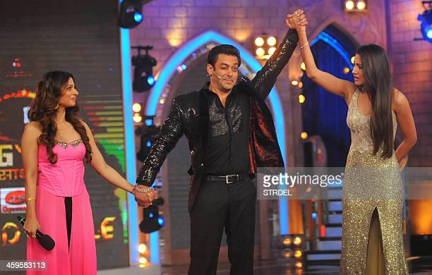 Indian Bollywood actor Salman Khan raises Indian actress Gauhar Khan to declare her as winner while actress Tanisha Mukherjee looks on as runnersup...
