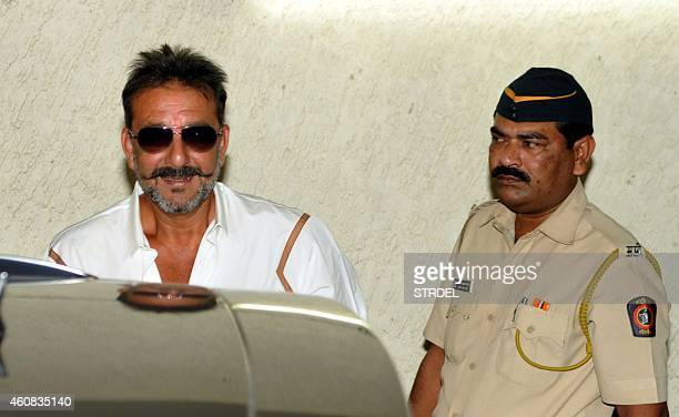 Indian Bollywood actor Sanjay Dutt on two weeks furlough from his prison sentence is escorted by police as he attends a special screening of his...