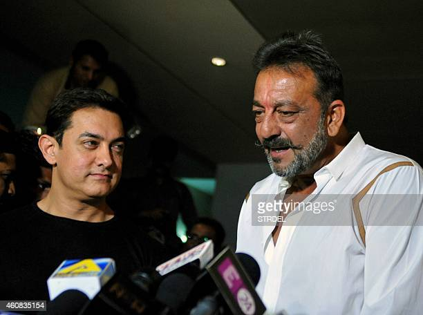 Indian Bollywood actor Sanjay Dutt on two weeks furlough from his prison sentence speaks to journalists with actor Aamir Khan as they attend a...