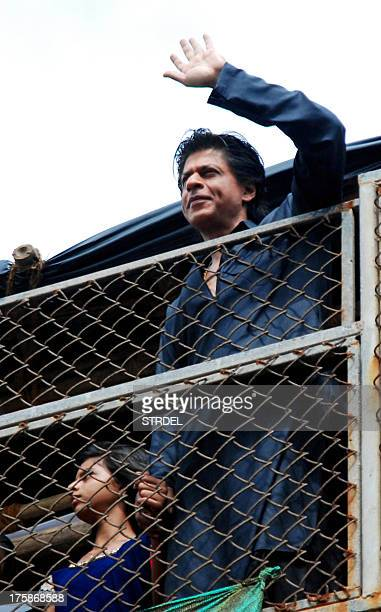 Indian Bollywood actor Shah Rukh Khan pictured with his daughter Suhana waves as he greets fans gathered outside his residence during the Muslim...