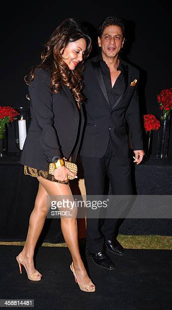 Indian Bollywood actor Shah Rukh Khan poses with his wife Gauri Khan as they arrive to attend a party hosted by actress Deepika Padukone in Mumbai...