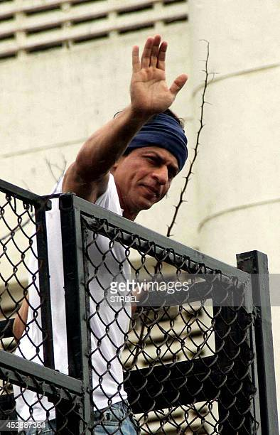 Indian Bollywood actor Shah Rukh Khan waves as he greets fans gathered outside his residence during the Muslim festival of Eid alFitr in Mumbai on...