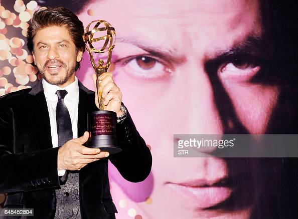 Indian Bollywood actor Shah Rukha Khan poses for a photograph with a National Yash Chopra Memorial Award in Mumbai on late February 25 2017 / AFP /...
