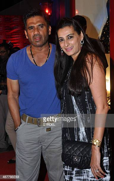 Indian Bollywood actor Suniel Shetty poses with his wife Mana Shetty as they attend the opening of a luxury boutique in Mumbai late December 18 2013...