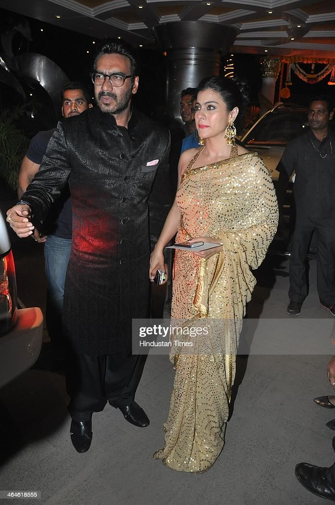 Indian Bollywood actors Ajay and Kajol Devgn during the wedding reception of Bollywood playback singer Raghav Sachar and actor Amita Pathak on January 21, 2014 in Mumbai, India.