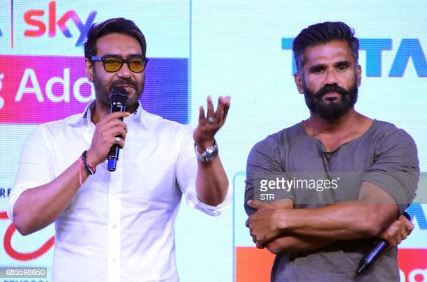 Indian Bollywood actors Ajay Devgn and Suniel Shetty talk onstage during the launch of 'Acting Adda' in Mumbai on 16 May 2017 / AFP PHOTO / STR