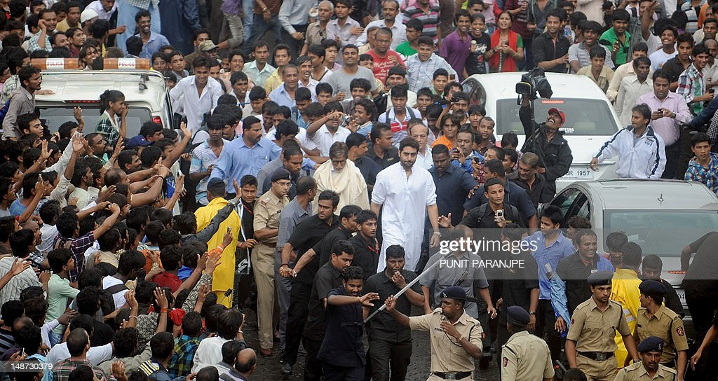 Indian Bollywood actors Amitabh Bachchan (C,left) along with his son Abhishek (C,right) surrounded by bodyguards and fans, arrive at a crematorium to pay their last respects to legendary actor Rajesh Khanna in Mumbai on July 19, 2012. Thousands of mourners thronged the streets of Mumbai under heavy monsoon rain to bid farewell and catch a final glimpse of Bollywood superstar Rajesh Khanna, who was cremated on July 19. AFP PHOTO/ Punit PARANJPE