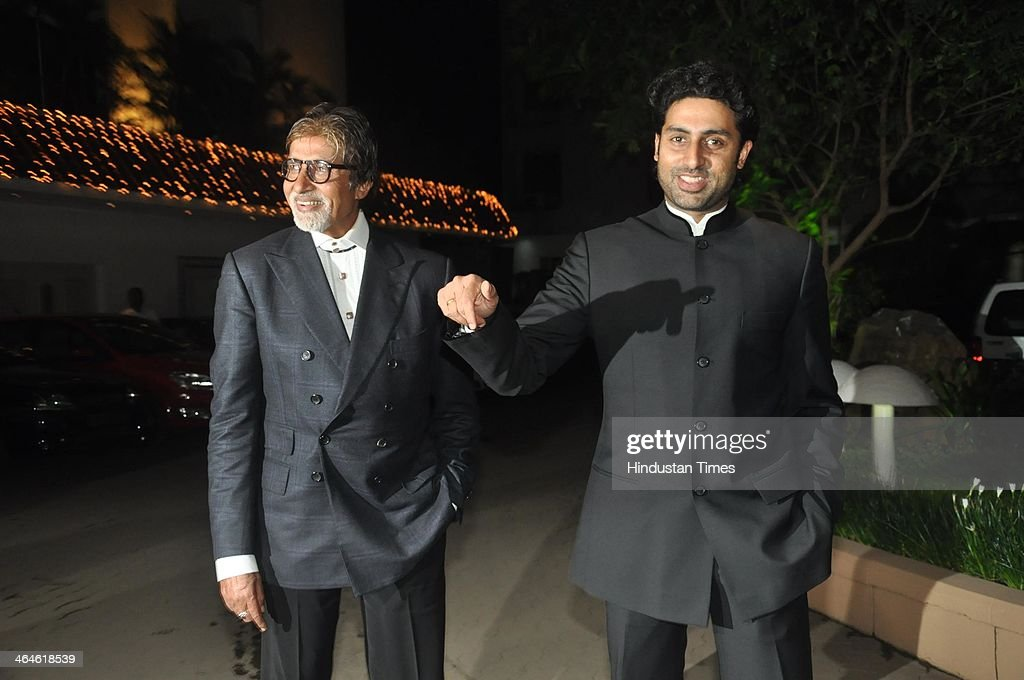 Indian Bollywood actors Amitabh Bachchan and Abhishek Bachchan during the wedding reception of Bollywood playback singer Raghav Sachar and actor Amita Pathak on January 21, 2014 in Mumbai, India.