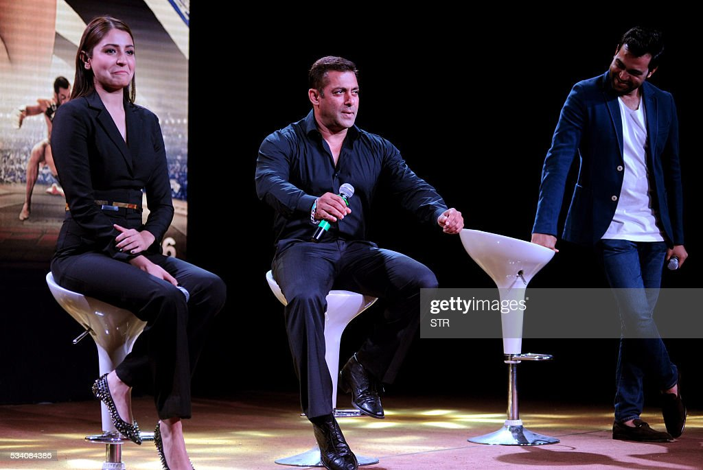 Indian Bollywood actors Anushka Sharma (L) and Salman Khan take part in a promotional event for the forthcoming Hindi film 'Sultan' directed by Ali Abbas Zafar (R) in Mumbai on late May 24, 2016. / AFP / STR